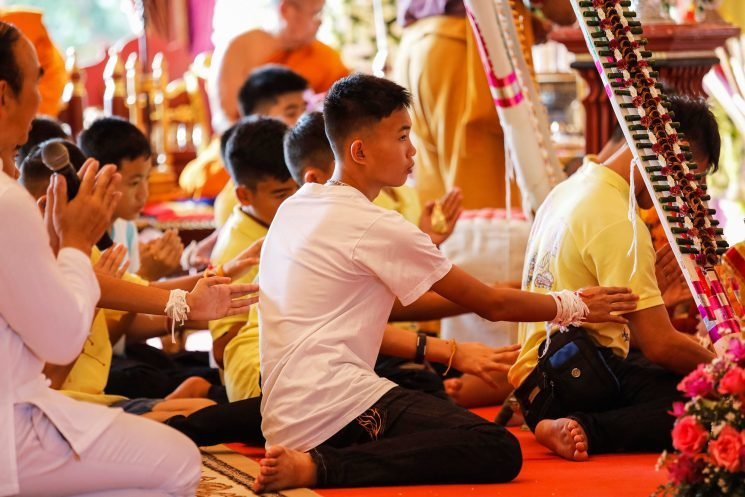 Rescued soccer kids pray for safety while visiting Buddhist temple