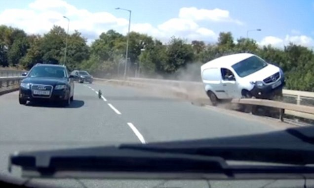 White van flips onto overpass guardrail then nearly tumbles onto A38