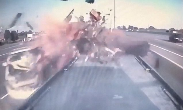 Car smashes into truck – sending tyres and crumpled metal flying