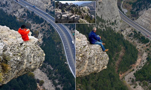 Daredevil pair pose for holiday snap on edge of 5,000ft rock face