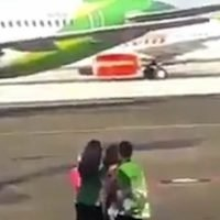 Woman CHASE plane on runway before being tackled by staff in Bali