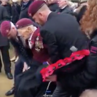 Heartwarming Remembrance Day moment two younger vets help paratrooper in wheelchair to his feet to salute fallen comrades