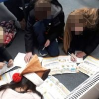 Shivering pupils pictured huddled around electric heater in icy classroom