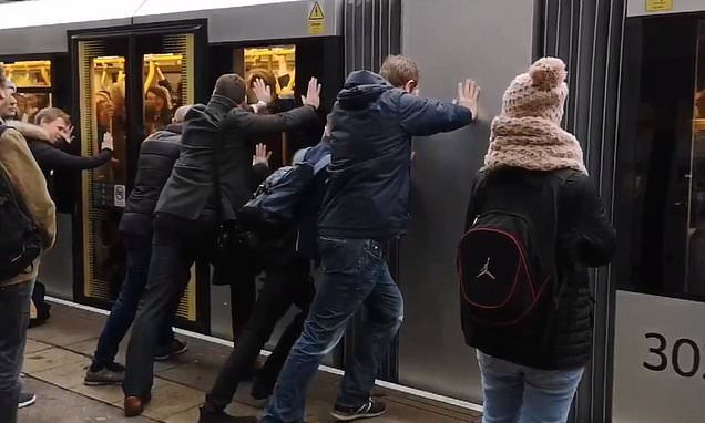 Staff ask rush hour commuters to give their overcrowded tram a SHOVE