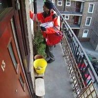 Postman pushes a parcel through a flat's open bathroom WINDOW