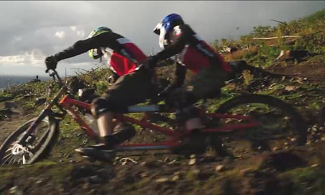 Mountain bikers hurtle over jumps and obstacles on a TANDEM