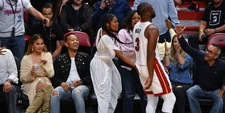 Dwyane Wade Celebrates Final Home Game By Colliding With Courtside John Legend and Chrissy Teigen